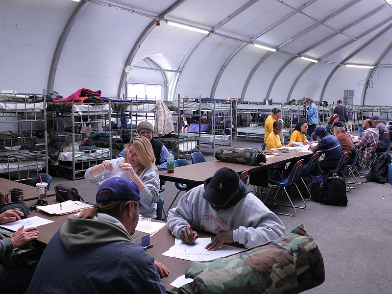Homeless vets sign in and dress their bunks as the San Diego Veterans Winter ...