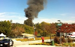 Smoke is seen in Escondido as authorities set fire to a home they said was so...