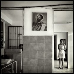 A young mother stands in the entryway to a shelter in Mexico, 2004.