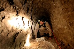A Homeland Security Special Agent, who chose to remain unidentified, crawls through a drug tunnel found by agents at a warehouse in Otay Mesa near the U.S.-Mexico border on Thursday, November 4, 2010.