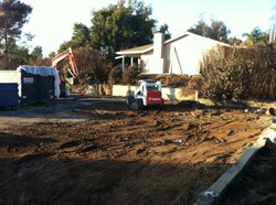 Crews clean up the burn site of the 'bomb home' after it was set ablaze by officials on December 9, 2010 in Escondido, California. Jakubec was arrested after authorities discovered the largest supply of explosive materials in one location in United States history in his house.