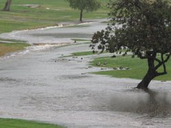 A river of rain water gushes through the Mission Trails Golf Course after fou...