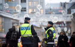 Swedish police officers patrol a street in central Stockholm, near where a su...
