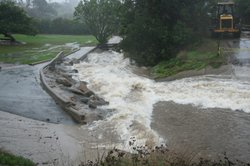 A rushing channel is created as storm drains overflow and can no longer handle the water in the flooded Mission Trails Golf Course, in the San Carlos neighborhood of San Diego.