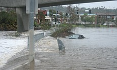 A Porsche is trapped on Mission Center Road as the San Diego River overwhelmed it's banks and closed many roads.