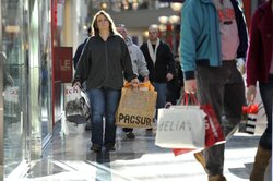 Customers carry bags of merchandise through Bridgewater Commons Mall December 24, 2010 in Bridgewater TWP, New Jersey. Shoppers brave cold temperatures and gusty winds to take care of last-minute shopping needs preparing for upcoming holidays.