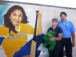 Tanya Lozoya's parents stand by a mural of their daughter in her softball uni...
