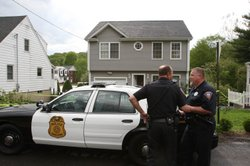 Police stand outside a former home, which was forclosed on, owned by Faisal Shahzad is seen May 4, 2010 in Shelton, Connecticut. Faisal Shahzad, 30, a suspect in this past weekend's failed car bomb plot in Times Square was taken into custody late Monday by FBI agents and New York Police Department detectives while trying to leave the country at John F. Kennedy Airport.