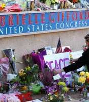 A woman repositions a sign at a makeshift memorial outside of the District Office of U.S. Rep. Gabrielle Giffords (D-AZ) a day after a gunman allegedly opened fire during a public event entitled 'Congress on your Corner' at the Safeway store on West Ina and North Oracle roads on January 9, 2011 in Tucson, Arizona.