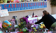 A woman repositions a sign at a makeshift memorial outside of the District Of...