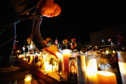 People light candles at a makeshift memorial that continues to grow in front ...