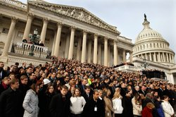 A crowd including members of Congress and their staff gather on the East Step...