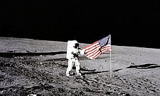 "Apollo 12 astronaut Charles ""Pete"" Conrad stands beside the United States flag after is was unfurled on the lunar surface during the first extravehicular activity (EVA-1), on November 19, 1969. Several footprints made by the crew can be seen in the photograph."