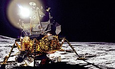 "A front view of the Apollo 14 Lunar Module ""Antares"", which reflects a circular flare caused by the brilliant sun. The unusual ball of light was said by the astronauts to have a jewel-like appearance. At extreme left, the lower slope of Cone Crater can be seen."