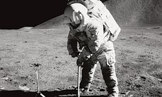 Astronaut James B. Irwin, lunar module pilot, uses a scoop in making a trench...