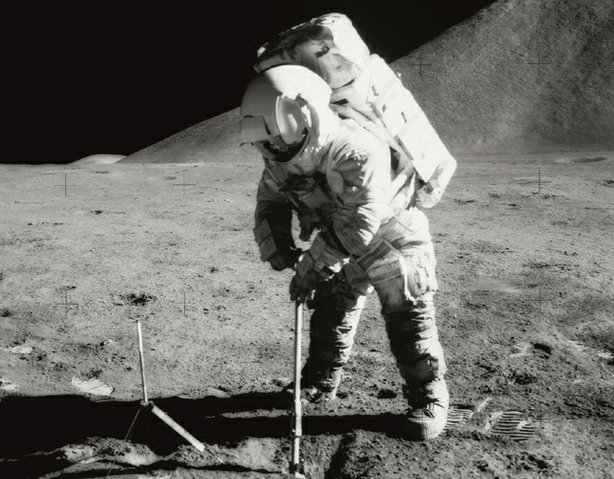 Astronaut James B. Irwin, lunar module pilot, uses a scoop in making a trench in the lunar soil during Apollo 15 extravehicular activity (EVA). Mount Hadley rises approximately 14,765 feet (about 4,500 meters) above the plain in the background.
