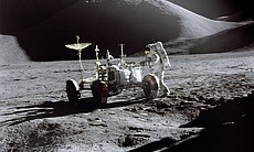 "Astronaut James B. Irwin, Lunar Module pilot, works at the Lunar Roving Vehicle during the first Apollo 15 lunar surface extravehicular activity (EVA-1) at the Hadley-Apennine landing site. The shadow of the Lunar Module ""Falcon"" is in the foreground. This view is looking northeast, with Mount Hadley in the background. This photograph was taken by Astronaut David R. Scott, Commander."