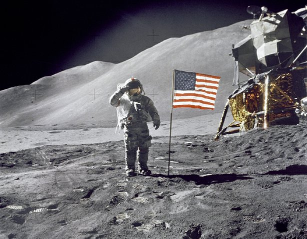 "Astronaut David R. Scott, commander, gives a military salute while standing beside the deployed U.S. flag during the Apollo 15 lunar surface extravehicular activity (EVA) at the Hadley-Apennine landing site. The flag was deployed toward the end of EVA-2. The Lunar Module ""Falcon"" is partially visible on the right. Hadley Delta in the background rises approximately 4,000 meters (about 13,124 feet) above the plain. The base of the mountain is approximately 5 kilometers (about 3 statute miles) away. This photograph was taken by Astronaut James B. Irwin, Lunar Module pilot."
