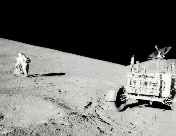 "Astronaut David R. Scott, mission commander, with tongs and gnomon in hand, studies a boulder on the slope of Hadley Delta during the Apollo 15 lunar surface extravehicular activity. The Lunar Roving Vehicle (LRV) or Rover is in right foreground. View is looking slightly south of west. ""Bennett Hill"" is at extreme right. Astronaut James B. Irwin, lunar module pilot, took this photograph."