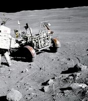 "Apollo 16 astronaut Charles M. Duke Jr., pilot of the Lunar Module ""Orion"", stands near the Rover, Lunar Roving Vehicle (LRV) at Station no. 4, near Stone Mountain, during the second Apollo 16 extravehicular activity (EVA-2) at the Descartes landing site. Light rays from South Ray crater can be seen at upper left. The gnomon, which is used as a photographic reference to establish local vertical Sun angle, scale, and lunar color, is deployed in the center foreground. Note angularity of rocks in the area."