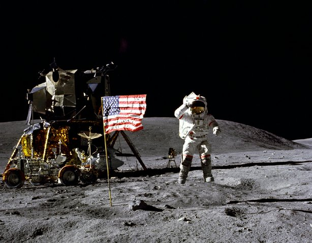 "Astronaut John W. Young, commander of the Apollo 16 lunar landing mission, jumps up from the lunar surface as he salutes the U.S. Flag at the Descartes landing site during the first Apollo 16 extravehicular activity (EVA-1). Astronaut Charles M. Duke Jr., lunar module pilot, took this picture. The Lunar Module (LM) ""Orion"" is on the left. The Lunar Roving Vehicle is parked beside the LM. The object behind Young in the shade of the LM is the Far Ultraviolet Camera/Spectrograph. Stone Mountain dominates the background in this lunar scene."