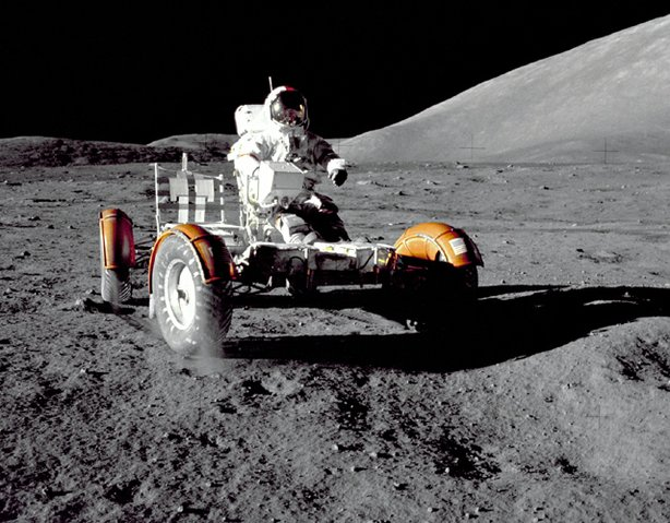"Astronaut Eugene A. Cernan, Apollo 17 mission commander, makes a short checkout of the Lunar Roving Vehicle during the early part of the first Apollo 17 extravehicular activity (EVA-1) at the Taurus-Littrow landing site. This view of the ""stripped down"" Rover is prior to loadup. This photograph was taken by Geologist-Astronaut Harrison H. Schmitt, Lunar Module pilot. The mountain in the right background is the East end of South Massif."