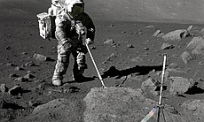 "Geologist-Astronaut Harrison Schmitt, Apollo 17 lunar module pilot, uses an adjustable sampling scoop to retrieve lunar samples during the second extravehicular activity (EVA-2), at Station 5 at the Taurus- Littrow landing site. The cohesive nature of the lunar soil is born out by the ""dirty"" appearance of Schmitt's space suit. A gnomon is atop the large rock in the foreground. The gnomon is a stadia rod mounted on a tripod, and serves as an indicator of the gravitational vector and provides accurate vertical reference and calibrated length for determining size and position of objects in near-field photographs. The color scale of blue, orange and green is used to accurately determine color for photography. The rod of it is 18 inches long. The scoop Dr. Schmitt is using is 11 3/4 inches long and is attached to a tool extension which adds a potential 30 inches of length to the scoop. The pan portion, blocked in this view, has a flat bottom, flanged on both sides with a partial cover on the top. It is used to retrieve sand, dust and lunar samples too small for the tongs. The pan and the adjusting mechanism are made of stainless steel and the handle is made of aluminum."