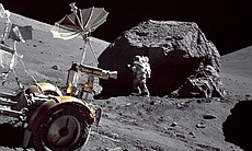 "Geologist-Astronaut Harrison H. Schmitt is photographed standing next to a huge, split boulder at Station 6 on the sloping base of North Massif during the third Apollo 17 extravehicular activity (EVA-3) at the Taurus-Littrow landing site. The ""Rover"" Lunar Roving Vehicle (LRV) is in the left foreground. Schmitt is the Apollo 17 Lunar Module pilot. This picture was taken by Commander Eugene A. Cernan."
