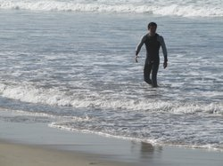 A surfer goes into the water at Imperial Beach, despite warnings of a major s...