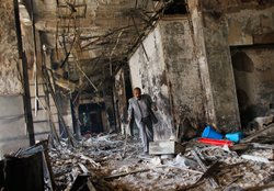 A man walks through the charred remains of a burned government building January 30, 2011 in Cairo, Egypt.