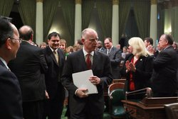 Members of the California State legislature applaud as California Governor Jerry Brown (C) arrives to deliver the State of the State address at the California State Capitol on January 31, 2011 in Sacramento, California.