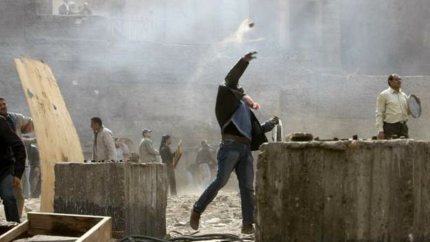 An Egyptian anti-government demonstrator battles pro-government opponents in ...