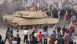 An army tank keeps Supporters of President Mubarak (top) separate from anti-g...