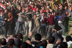 Anti-government protestors (front) clash with supporters of President Mubarak...