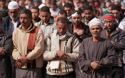 Anti-government demonstrators pray in Tahrir Square in sight of The Egyptian ...