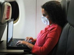An airline passenger wears a mask to protect against viruses. Passengers are ...
