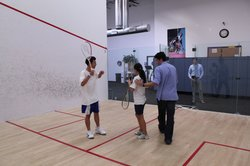 Squash coach Renato Paiva helps Access Youth Academy team members Ana Rodrigu...