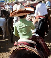 A young boy in full charro gear, with a shirt emblazoned with the city where his father rides: San Ysidro. Men are introduced to charreria from the time they're very little.