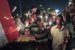 Anti-government protesters walk during a candlelight vigil for those killed during the uprising in Tahrir Square on February 9, 2011 in Cairo, Egypt.