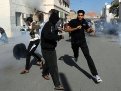 Bahraini protestors run for cover after police fired tear gas canisters to di...