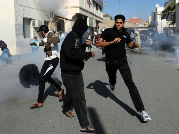 Bahraini protestors run for cover after police fired tear gas canisters to disperse them in the village of Diraz, northwest of Bahrain.