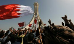 Bahraini protesters wave the national flag and chant slogans as they gather W...