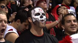 A fan adorned with face paint watches from the student section as the Aztecs play the University of New Mexico.