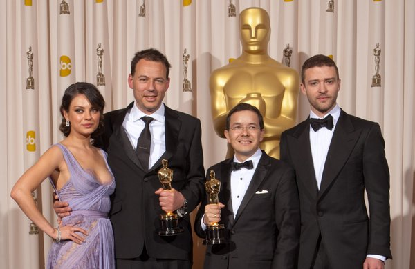 Mila Kunis and Justin Timberlake flank the Best Animated Short winners Shaun Tan and Andrew Ruhemann.