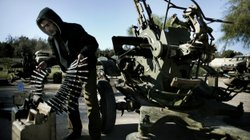 A Libyan civilian holds anti-aircraft ammunition at an army barrack in Bengha...