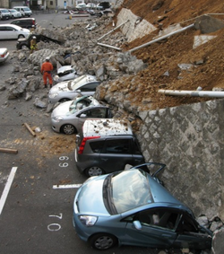 Vehicles are crushed by a collapsed wall at a carpark in Mito city in Ibaraki prefecture on March 11, 2011 after a massive earthquake rocked Japan. massive 8.9-magnitude earthquake hit Japan on March 11, unleashing a monster 10-metre high tsunami that sent ships crashing into the shore and carried cars through the streets of coastal towns. AFP PHOTO / JIJI PRESS (Photo credit should read JIJI PRESS/AFP/Getty Images)