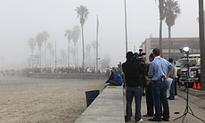 People gather along the shore in Ocean Beach to watch the tide after a tsunami warning went into effect following the 8.9 eathquake in Japan.