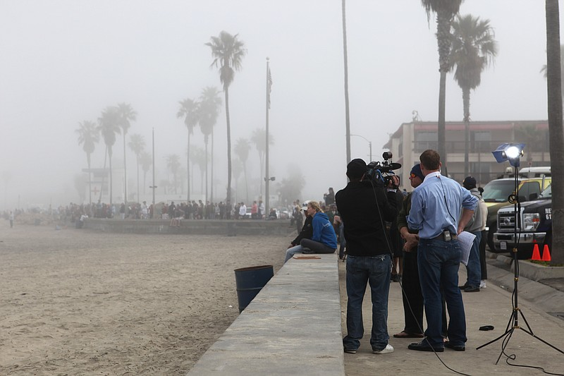 People gather along the shore in Ocean Beach to...