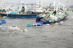 Fishing boats and vehicles are carried by a tsunami wave at Onahama port in I...