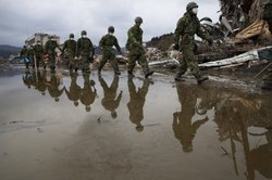 Japanese military march during a search and rescue mission scouring the rubbl...